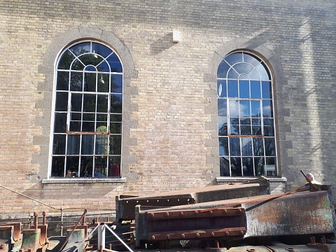 The largest pair of windows with opening lights with large areas of corrosion present around the opening light and frame joints.