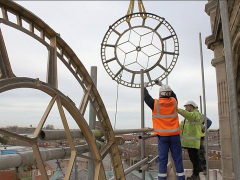 Lifting the restored clock faces back to their original positions.